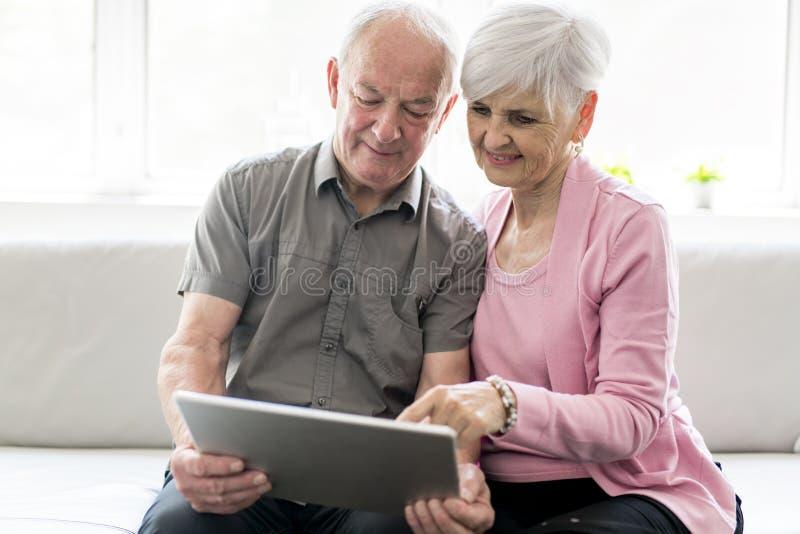 Hartelijke aantrekkelijke bejaarde paarzitting samen op een laag met tablet stock foto