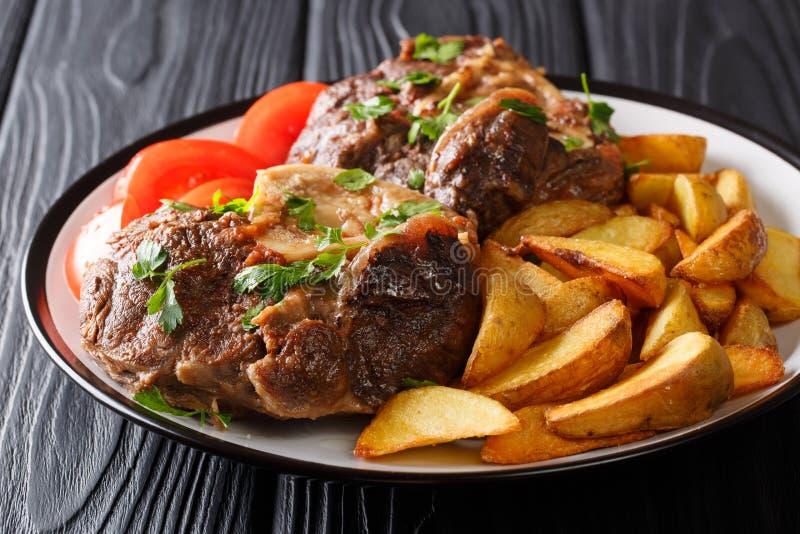 Hartelijke maaltijd: het kalfsvlees Ossobuco diende geroosterde aardappelplakken en fres stock afbeeldingen