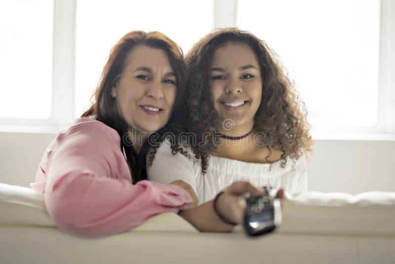 Hartelijke moeder en dochterzitting op bank het luisteren TV met ver royalty-vrije stock foto's