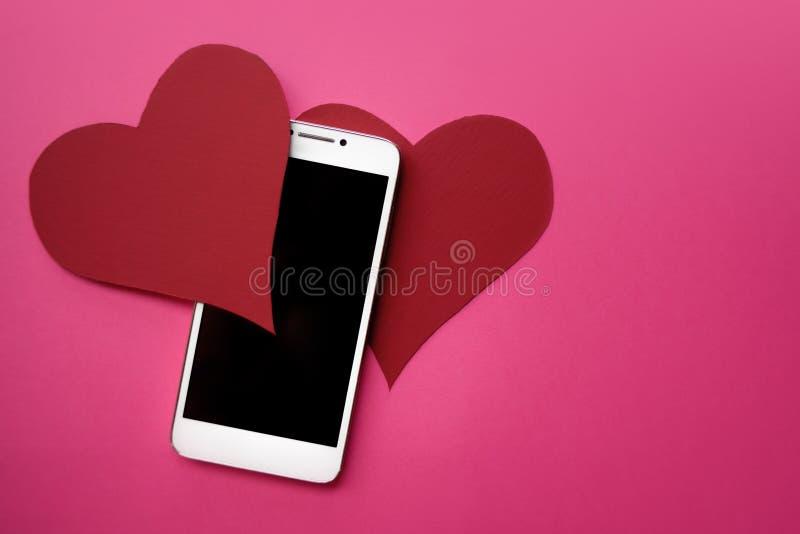 Harten en smartphone Het concept aan gelijkaardig in sociale netwerken of het Dateren van app Roze achtergrond stock foto