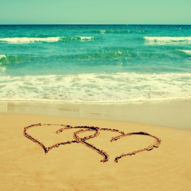 Harten in het zand van een strand stock afbeeldingen