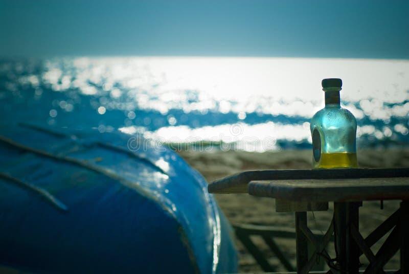 Harter Alkohol und Boot auf Strand stockfoto