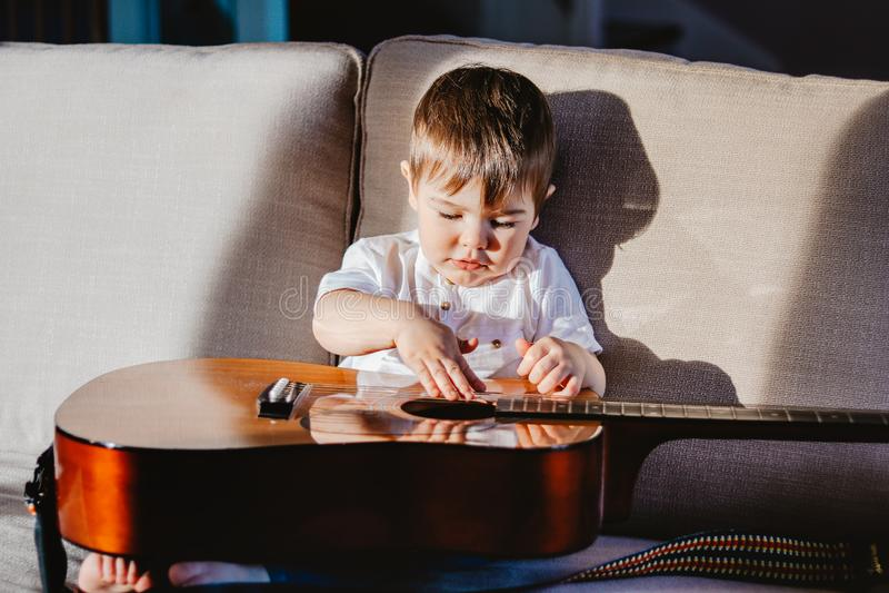 Hartes helles Porträt des netten kleinen Babys, das großes Gitarrensitzen auf Sofa spielt lizenzfreie stockbilder