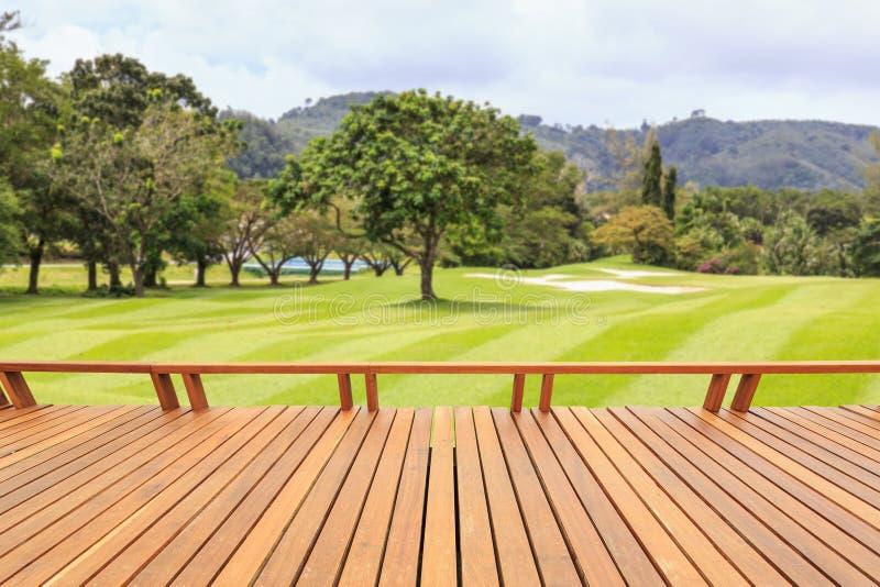Hartholz Decking oder Bodenbelag und Ansicht des grünen Feldes in Golf cou lizenzfreie stockbilder