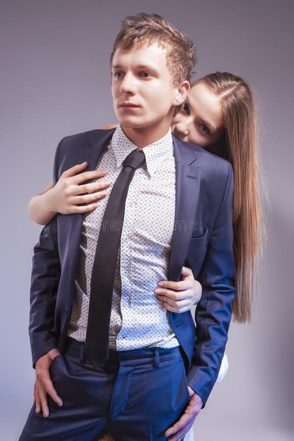 Hartstochtelijk Houdend van Kaukasisch Paar die samen spelen Vrouw het Verbergen achter de Mens tegen Grijs stock fotografie