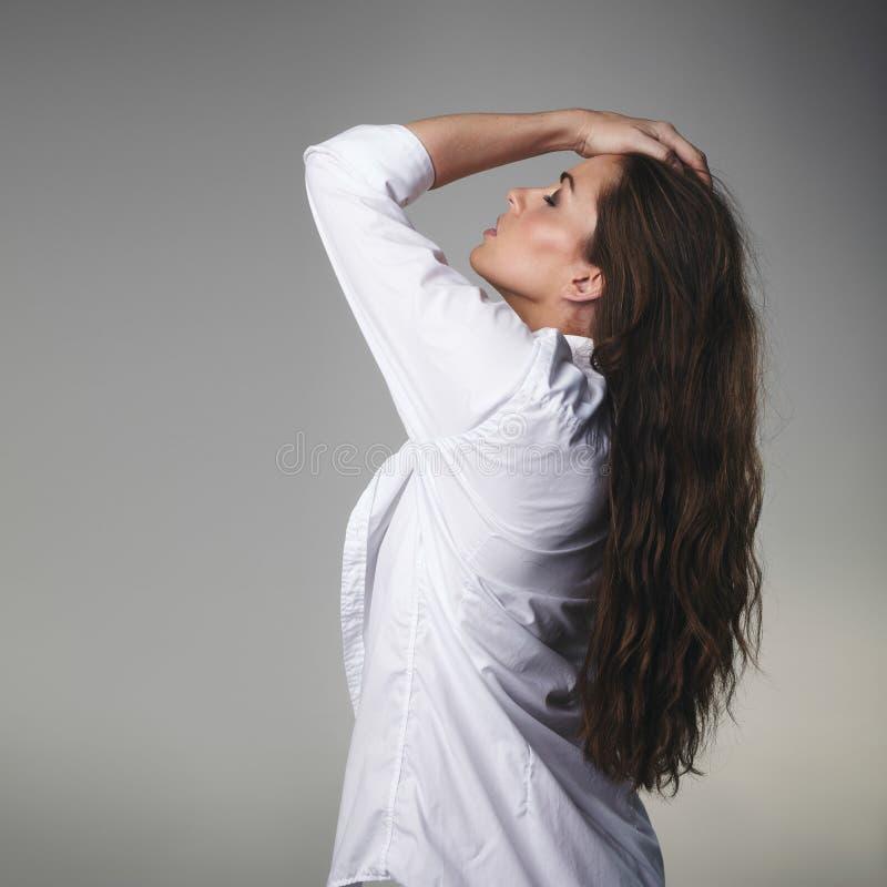 Hartstochtelijk jong brunette op grijze achtergrond stock afbeelding