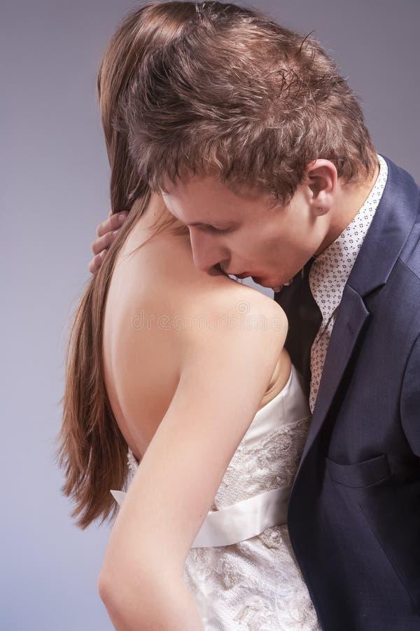 Hartstochtelijk Kaukasisch Paar die in Liefde samen kussen Vrouw het Stellen in Huwelijkskleding tegen Grijs stock afbeelding