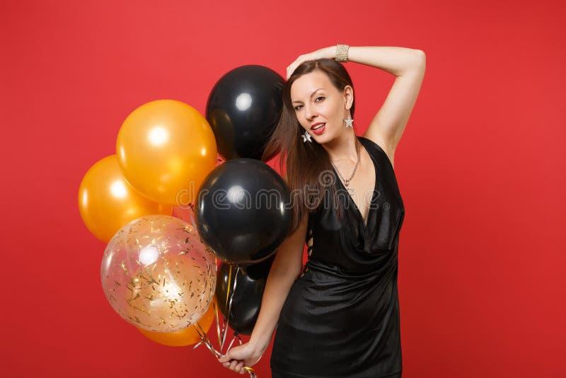 Hartstochts jong meisje dat in weinig zwarte kleding zettend hand op de hoofdballons viert van de greeplucht dat op rode achtergr royalty-vrije stock afbeelding