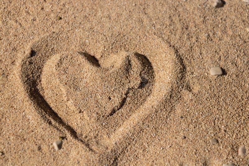 Hartvorm in het zand stock afbeeldingen