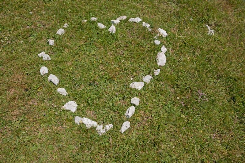 Hartvorm op grasachtergrond, van kleine stenen wordt gemaakt die royalty-vrije stock afbeelding
