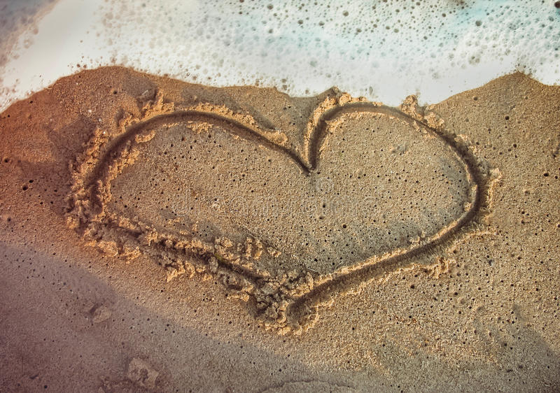 Hartvorm op het strand wordt getrokken dat royalty-vrije stock afbeelding