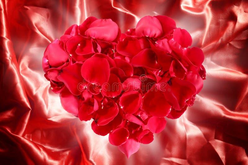 Hartvorm uit roze bloemblaadjes op rode stoffenzijde die wordt gemaakt stock foto's