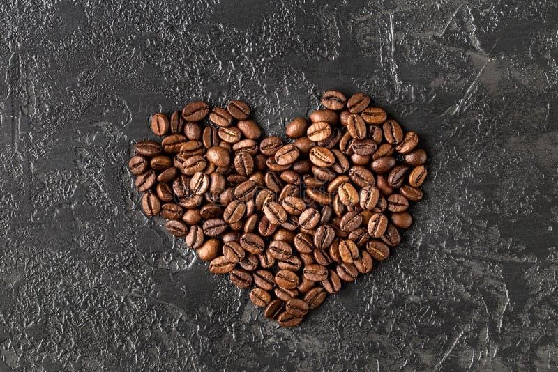 Hartvorm van geroosterde koffiebonen op donkere achtergrond royalty-vrije stock afbeelding