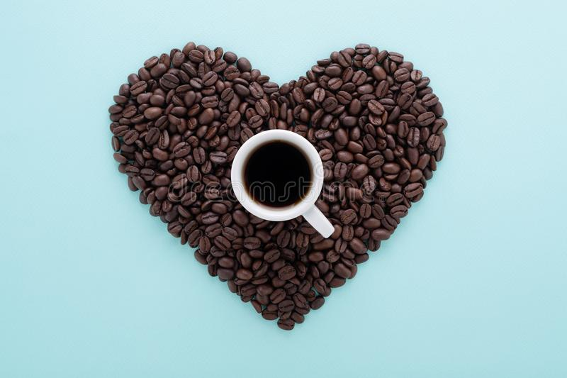 Hartvorm van koffiebonen & kop van koffie op blauw royalty-vrije stock foto's