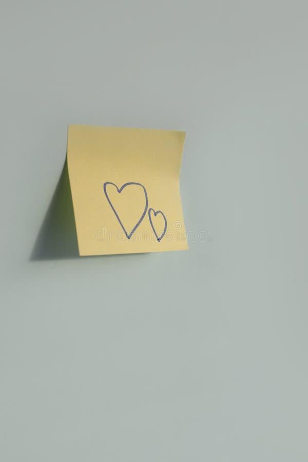 hartvormen met de hand geschreven op document sticker op de blauwe achtergrond royalty-vrije stock foto's