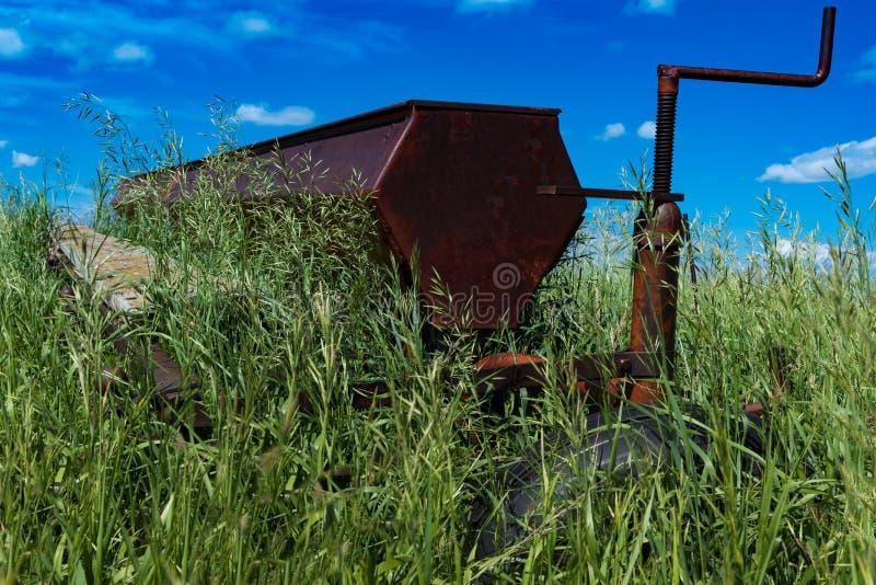 Harv för tappninglantbrukdiskett i ett fält som omges av högväxt gräs royaltyfri bild