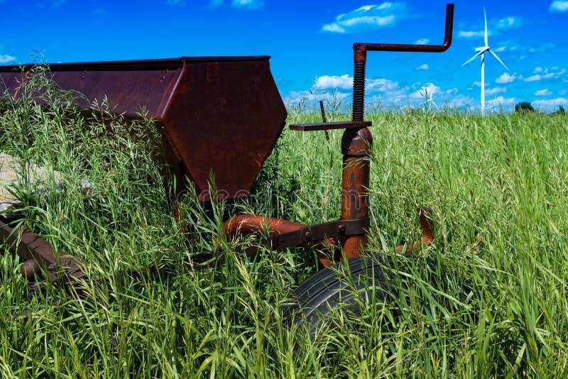 Harv för tappninglantbrukdiskett i ett fält som omges av högväxt gräs med vindturbiner royaltyfria bilder