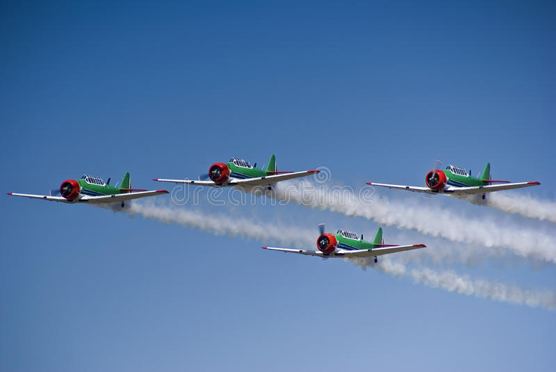 Harvard Aerobatic Team - Low Level Flyby. Harvard aerobatic team, in a display of four up formation flying, with smoke trails. 1/3 front Side view royalty free stock photos
