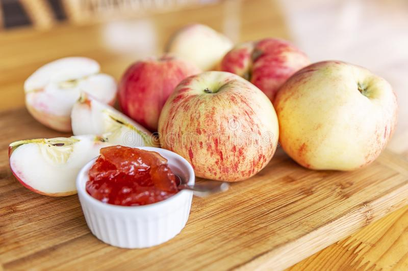 Harvest beautiful apples with red barrels and jam from them. Still life on a wooden board on the table. Horizontal stock photography