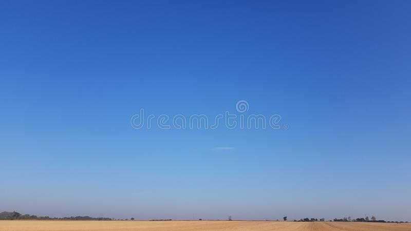 Harvest Blue North Norfolk Sky. Typical North Norfolk, UK landscape. Deep blue sky over a harvested field. A little Mist over the tree line royalty free stock images