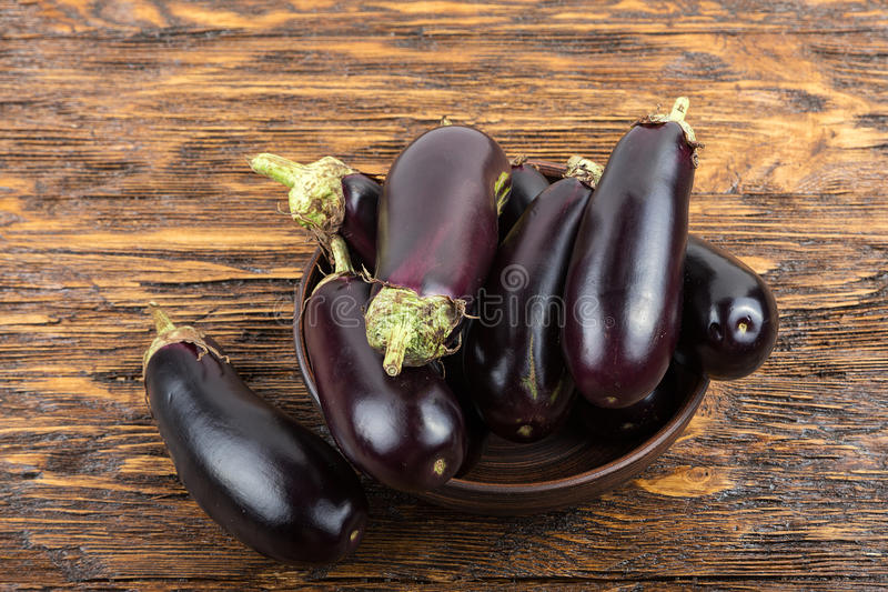 Harvest of eggplant on a wooden table. Harvest of eggplant in a clay plate on an old dark wood table stock photos