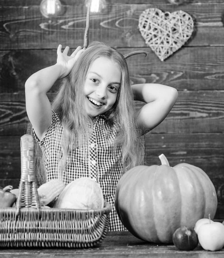 Harvest festival concept. Child little girl enjoy farm life. Organic gardening. Girl kid at farm market with organic. Vegetables. Kid farmer with harvest wooden stock photos