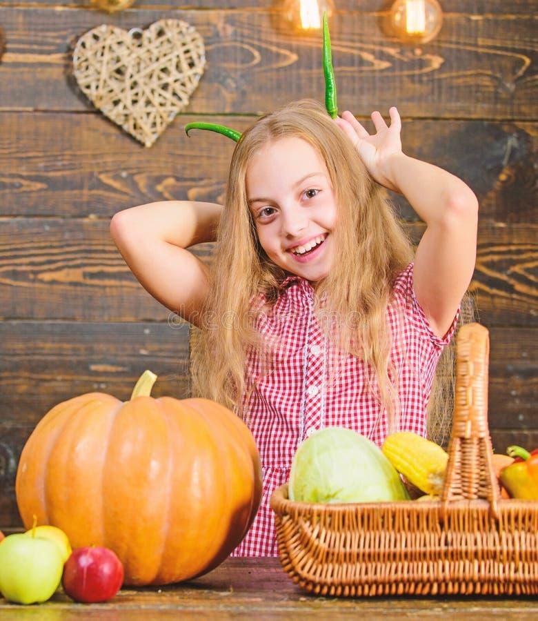 Harvest festival concept. Child little girl enjoy farm life. Organic gardening. Girl kid at farm market with organic. Vegetables. Kid farmer with harvest wooden stock image