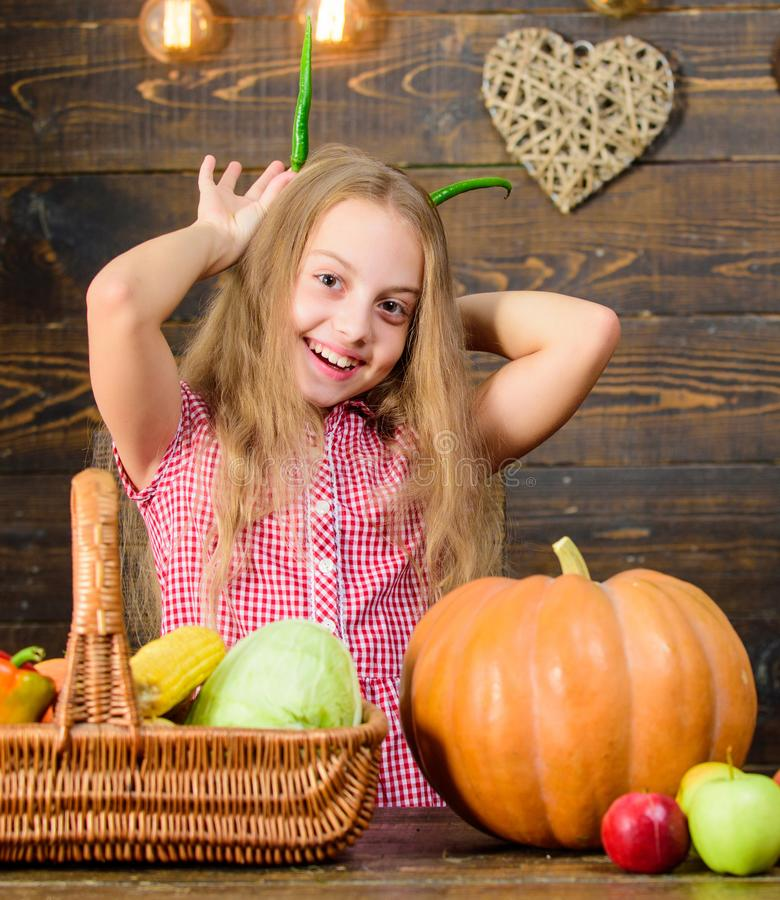 Harvest festival concept. Child little girl enjoy farm life. Organic gardening. Girl kid at farm market with organic. Vegetables. Kid farmer with harvest wooden stock photos