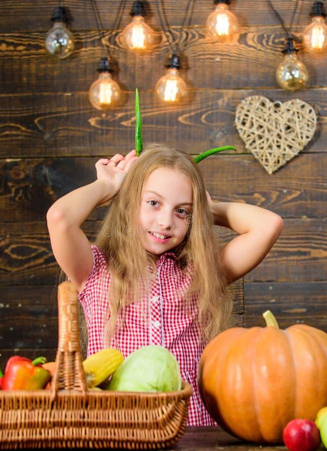 Harvest festival concept. Child little girl enjoy farm life. Organic gardening. Kid farmer with harvest wooden. Background. Grow your own organic food. Girl kid stock image