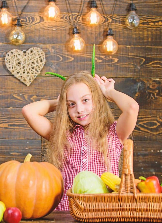 Harvest festival concept. Child little girl enjoy farm life. Organic gardening. Kid farmer with harvest wooden. Background. Grow your own organic food. Girl kid royalty free stock photos