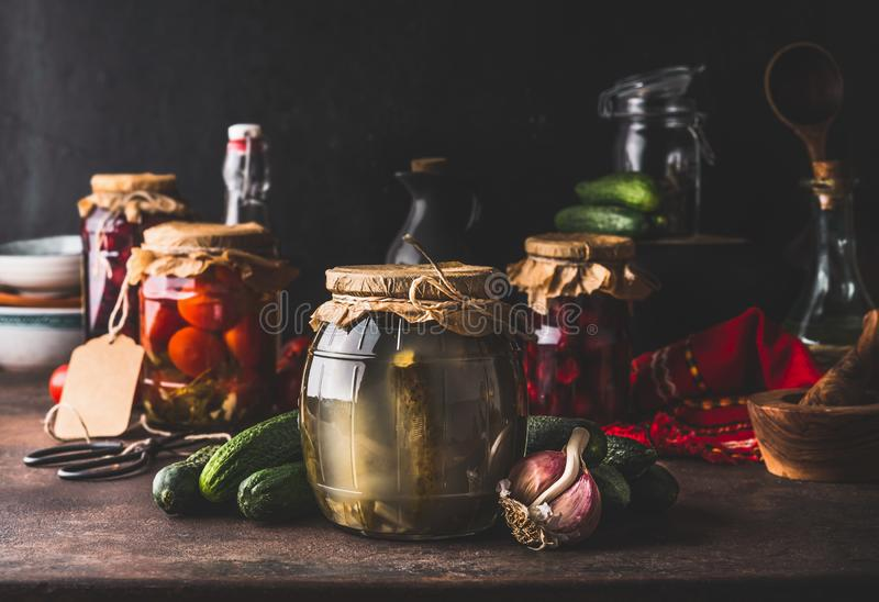 Harvest preserve concept. Glass jars with fermented, pickled and canned vegetables and fruits on dark rustic kitchen table. stock image