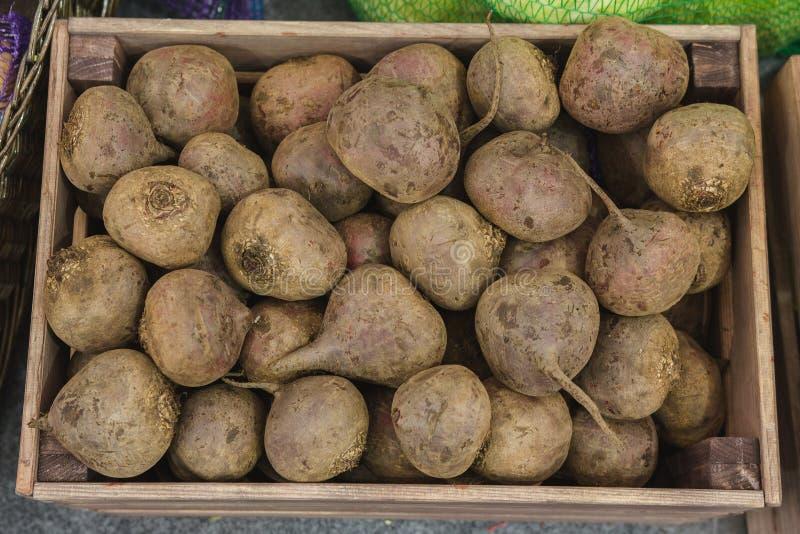 Harvest of sugar beet in a wooden basket at street market. Close up stock images