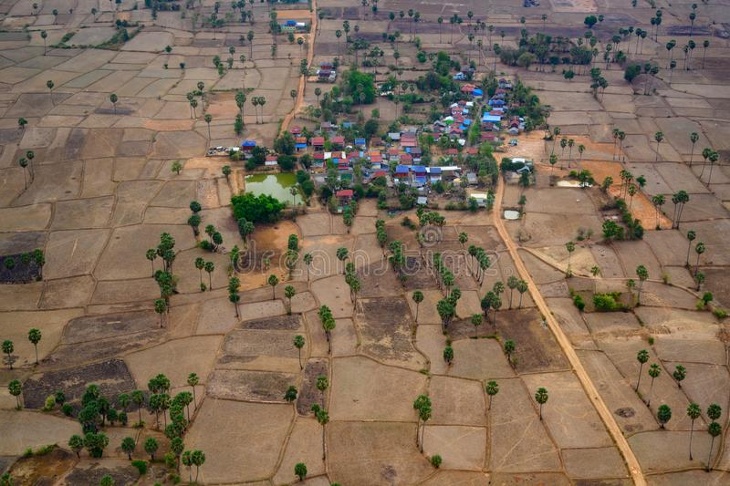 Small village surrounded by dry harvested rice fields, Cambodia. Aerial view of agrarian fields, Asia stock photo
