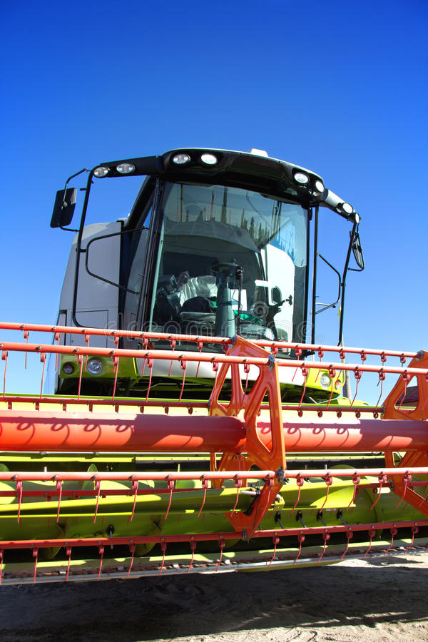 Harvester against the blue sky. Farming techniques, modern combine harvester against the blue sky, fertile land, agricultural production, combine harvests stock photography