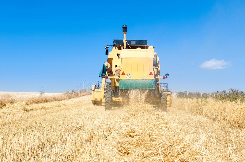 Harvester performing mowing tasks in the field. Harvester in the foreground on rustic background working in the field royalty free stock photography