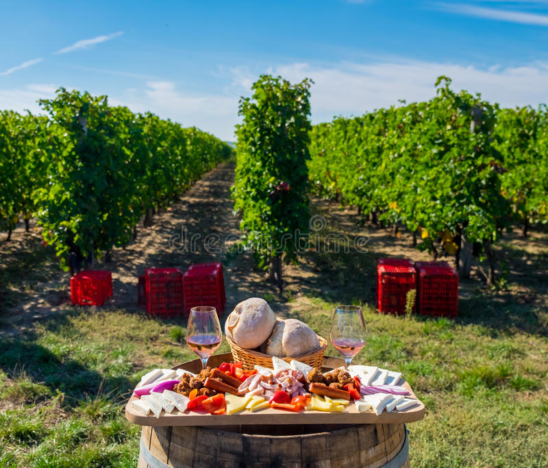 Harvesting season traditional Romanian food plate with cheese, b. Read, sausages, onions and red wine in glass in vineyards, on barell stock photos