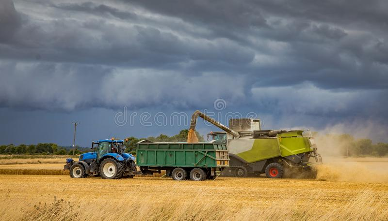 Harvesting under a very stormy looking sky. royalty free stock images