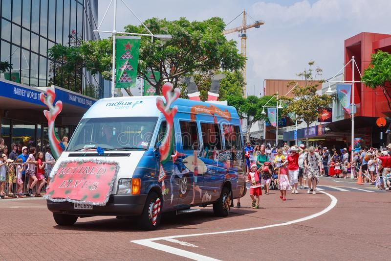 A rest home`s van taking part in a Christmas parade. It has been decorated with reindeer antlers and a sign reading `retired elves`. Photographed in downtown royalty free stock photo
