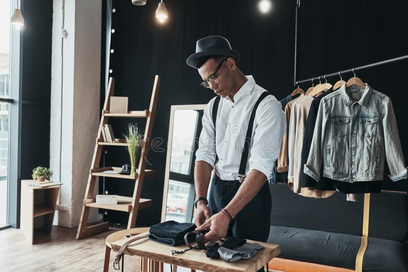 He has a great style. Serious young man arranging menswear while. Standing in the showroom royalty free stock photography