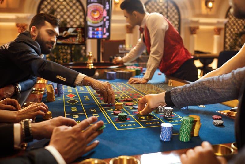 Hasardspelare för en grupp människor som spelar spela pokerrouletten i en kasino fotografering för bildbyråer