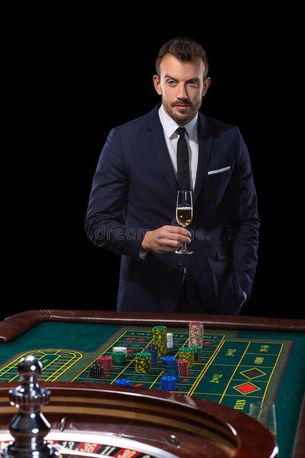 Hasardspelareinsatser som spelar på rouletttabellen Riskabel underhållning av dobblerit royaltyfri bild