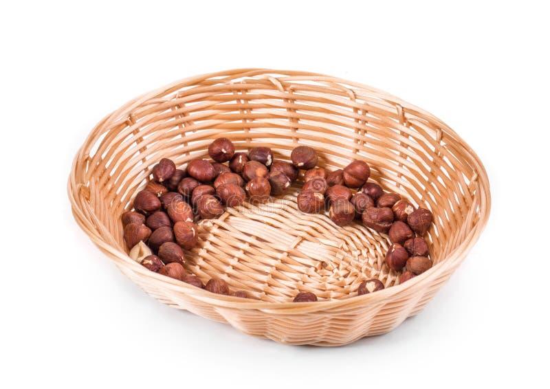 Haselnüsse auf einem Weidenkorb lizenzfreie stockfotos