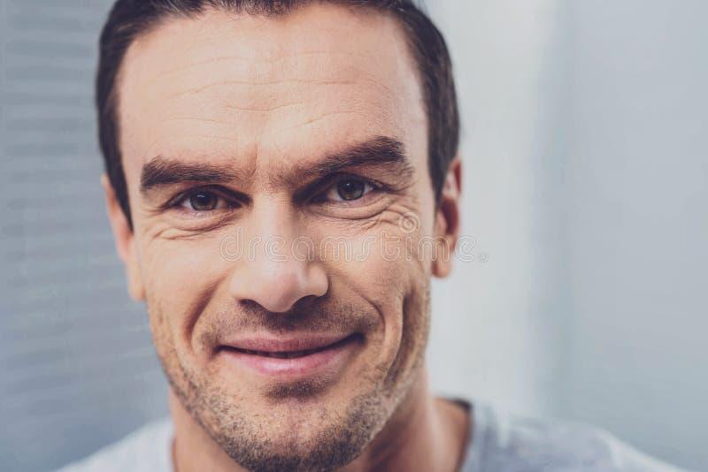 Haselnuss-äugiger gutaussehender Mann, der beim Betrachten geliebt lächelt lizenzfreies stockbild