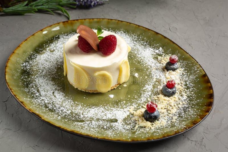Haselnussschokoladenkuchen mit den Schokoladenblumenbl?ttern und Eiscreme auf einer gr?nen Platte lizenzfreies stockfoto