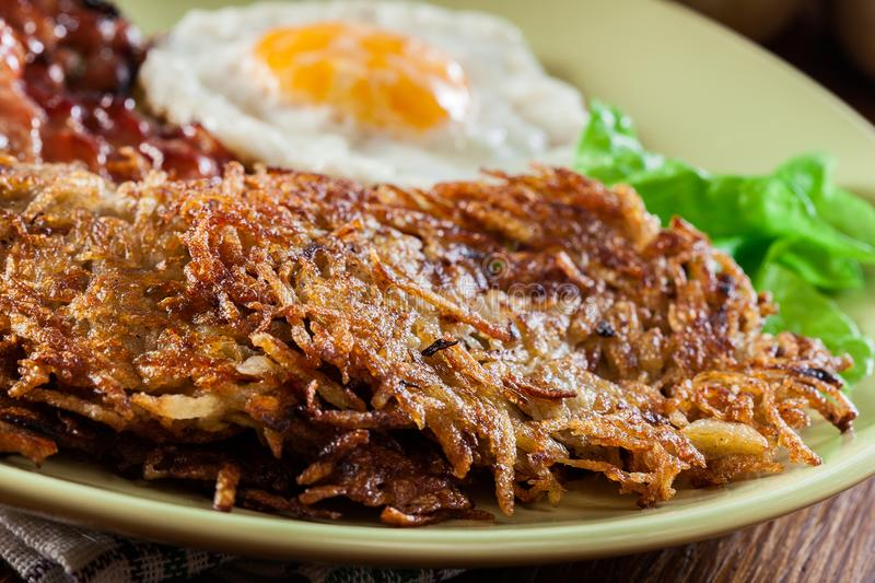 Hash browns. Potato pancakes with crispy fried bacon and fried egg stock photo