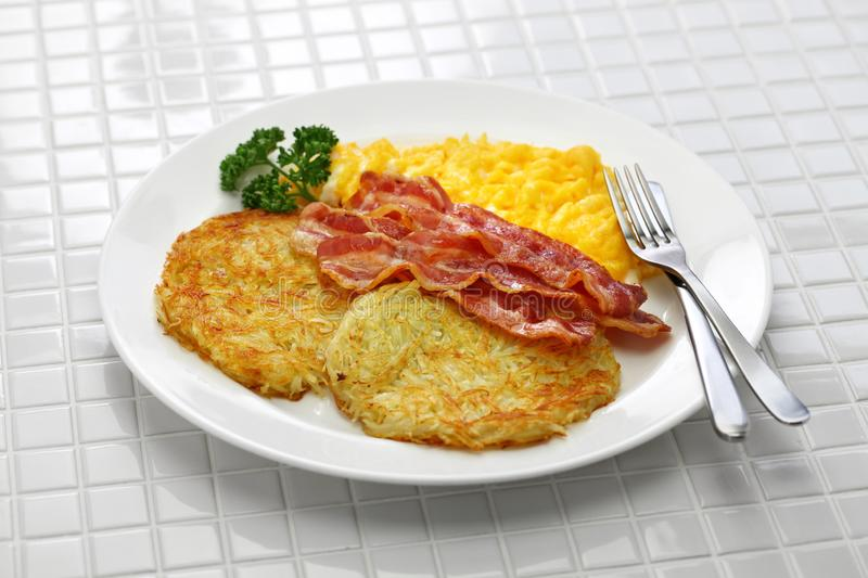 Hash browns, scrambled eggs and bacon royalty free stock images