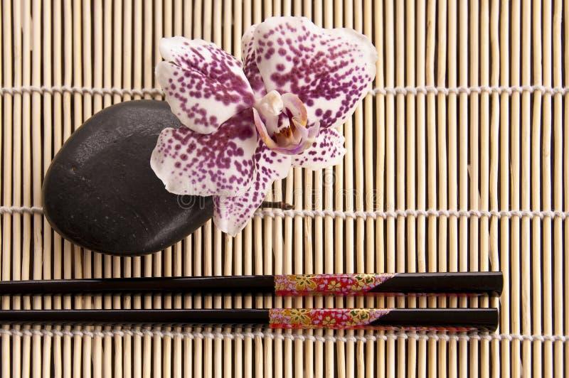Hashis com a flor preta da pedra e da orquídea foto de stock royalty free