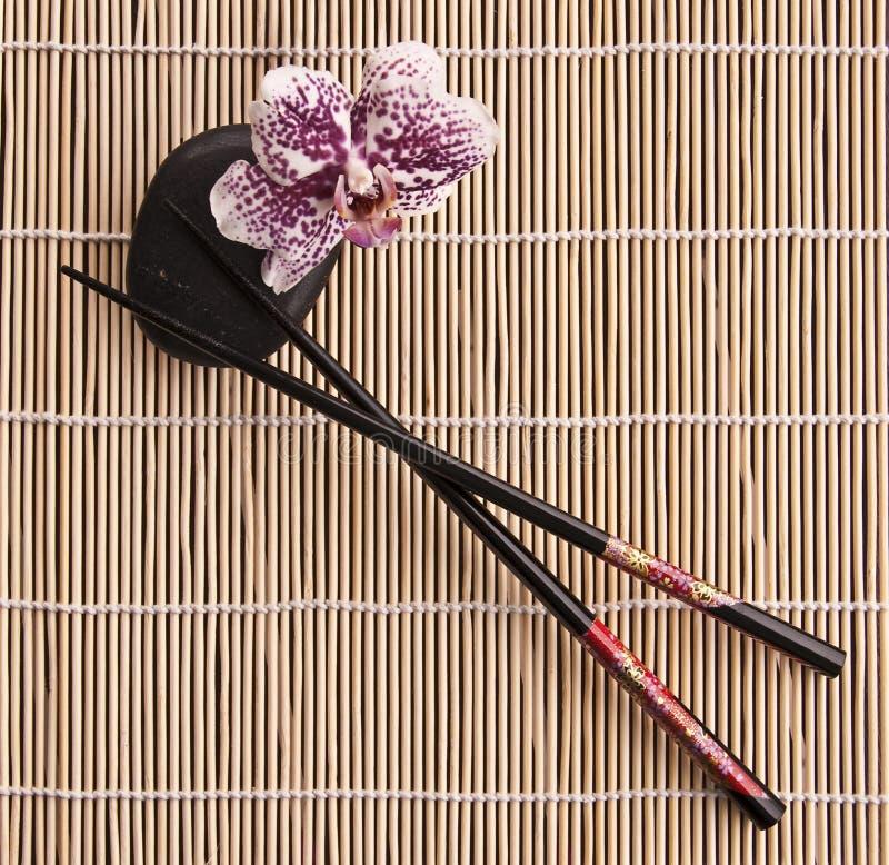 Hashis com a flor preta da pedra e da orquídea imagens de stock royalty free