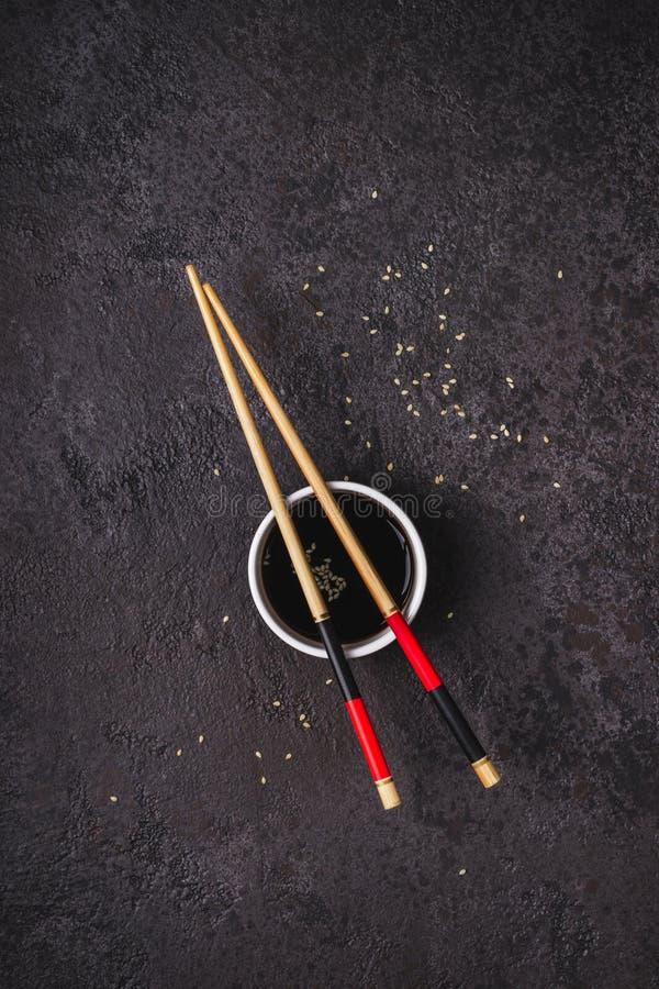 Hashis do bacia do molho de soja e os de bambu no fundo preto Conceito asiático da culinária fotos de stock royalty free