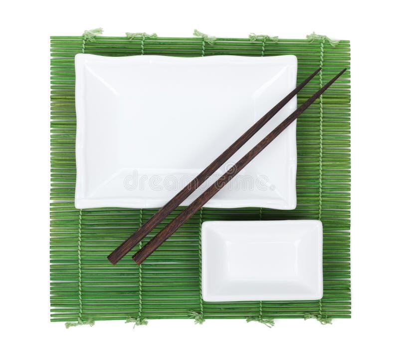 Hashis e utensílios sobre a esteira de bambu imagem de stock